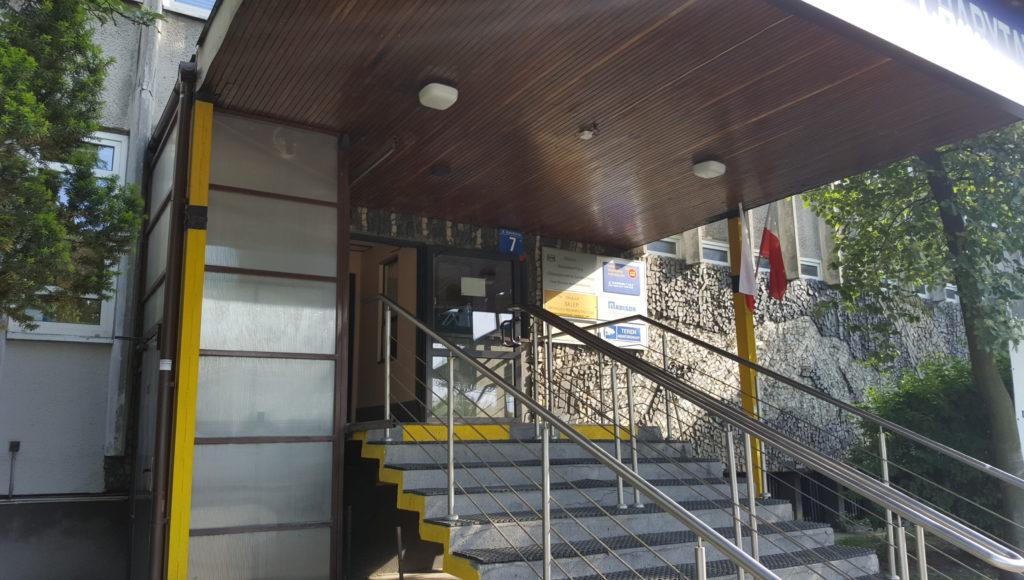 Znacznik przy wejściu do budynku przy Konwiktorskiej 7. Zamontowany między wejściem a windą. Ujęcie z daleka. Widać całe wejście i schody