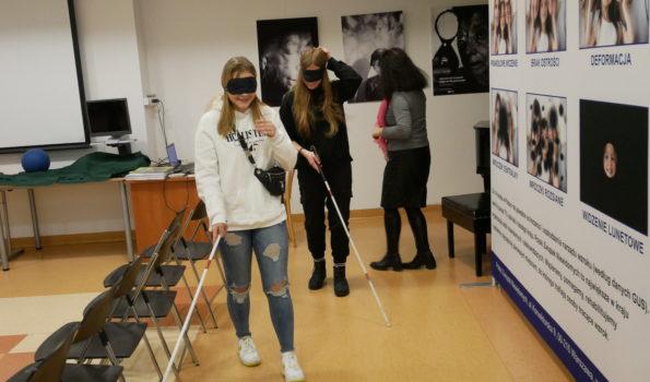 Tyflogaleria PZN. Zajęcia Laboratorium Ciemności. Dwie nastolatki trzymają przed sobą białe laski. Mają zasłonięte oczy.