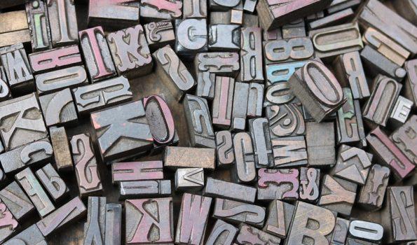 Porozrzucane mosiężn e litery o różnych kształtach.