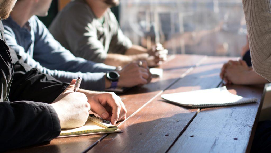 Zdjęcie. Kilka osób siedzi przy biurku podczas spotkania.