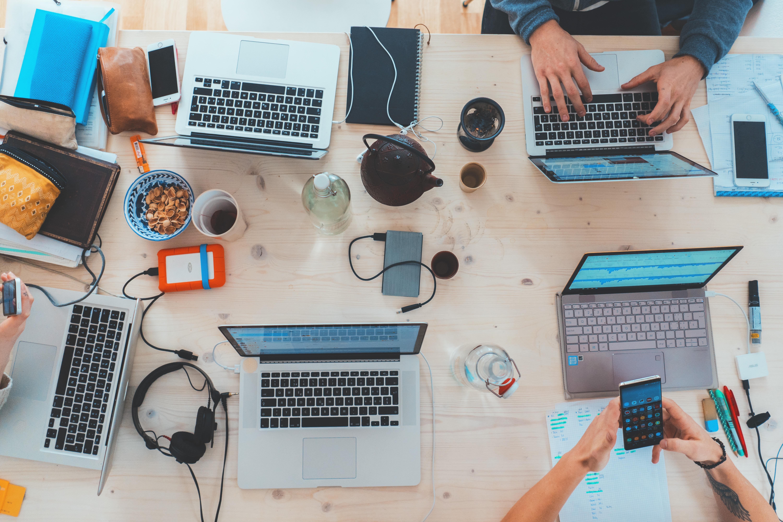 Pięć laptopów z otwartymi ekranami na stole. W różnych orientacjach (obok, przed, pomiędzy) lezą też inne przedmioty - słuchawki, smartfony, ładowarki, kubki.