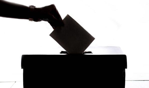 Zbliżenie na dłoń wkładającą kartę do głosowania do urny wyborczej