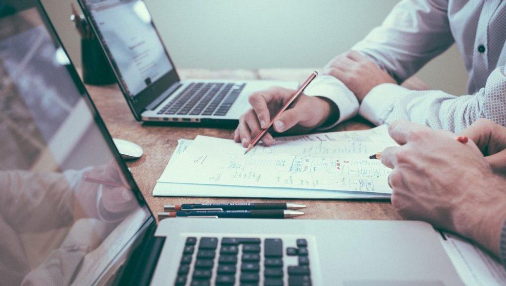 Spotkanie biznesowe. Dwie laptopy stoją na stole, pomiędzy nimi kartka, na której jedna z osób robi notatki.