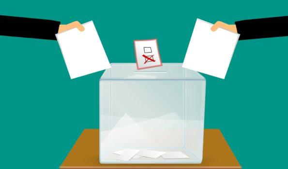 Rysunek: dwie osoby wrzucają swoje głosy do urny wyborczej