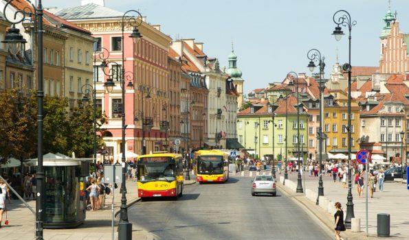 Dwa żółto-czerwone autobusy na ulicy Krakowskie Przedmieście. W tle plac Zamkowy. Fot. Pixabay
