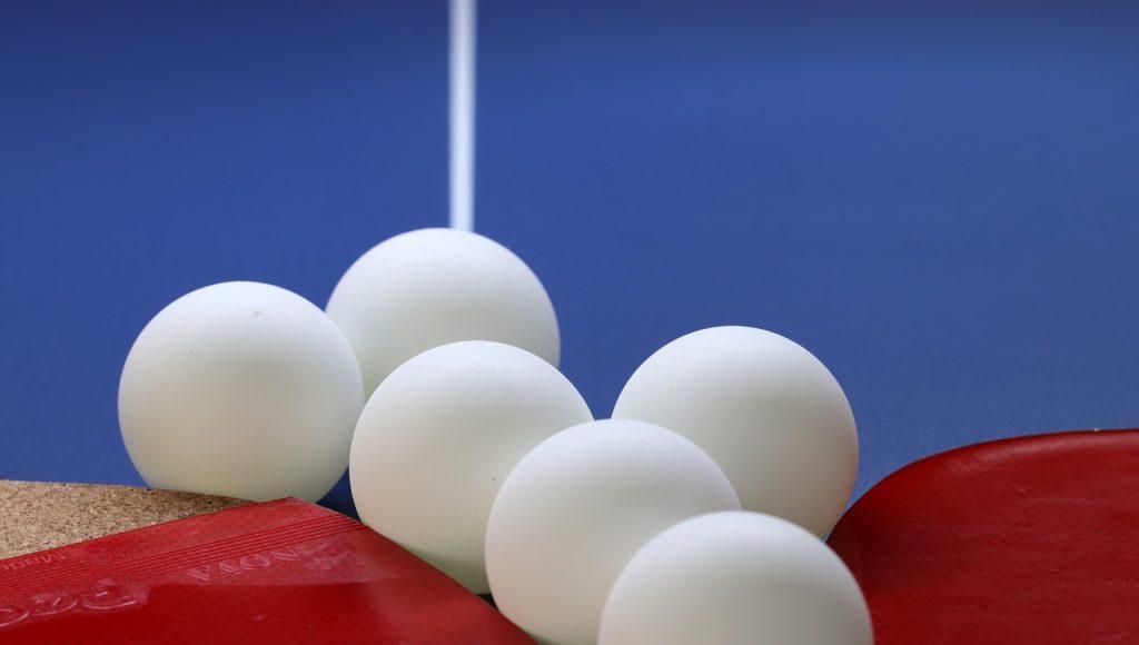 Sześć białych piłeczek ping-pongowych leżących na stole do tenisa stołowego. Fot. Pixabay