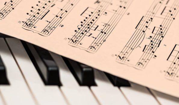 Biało-czarne klawisze fortepianu. Na nich leżą nuty.