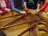 Ujęcie w przybliżeniu. Uczestnicy warsztatów dotykają strun instrumentu.