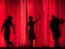 Scena, czerwone tło, widać cienie trzech aktorów