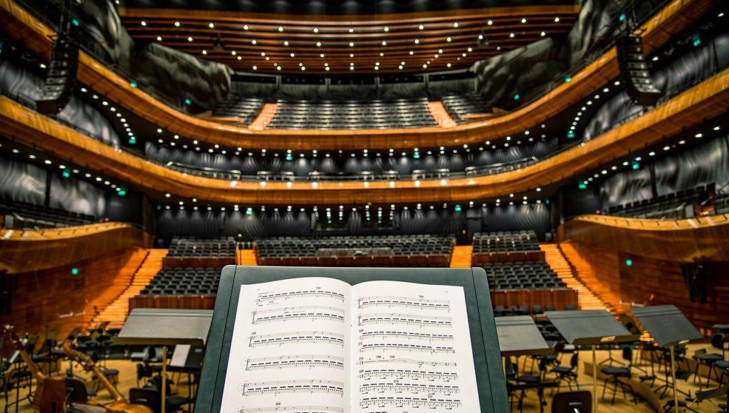 Partytura muzyczna w tle sala koncertowa