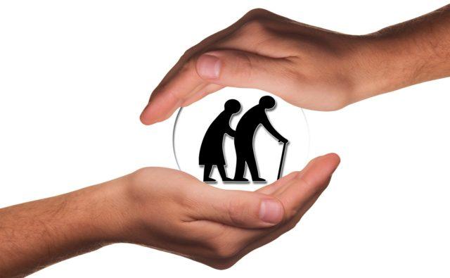 Grafika przedstawia dwie osoby starsze idące ramię w ramię. Objęte są dłońmi.