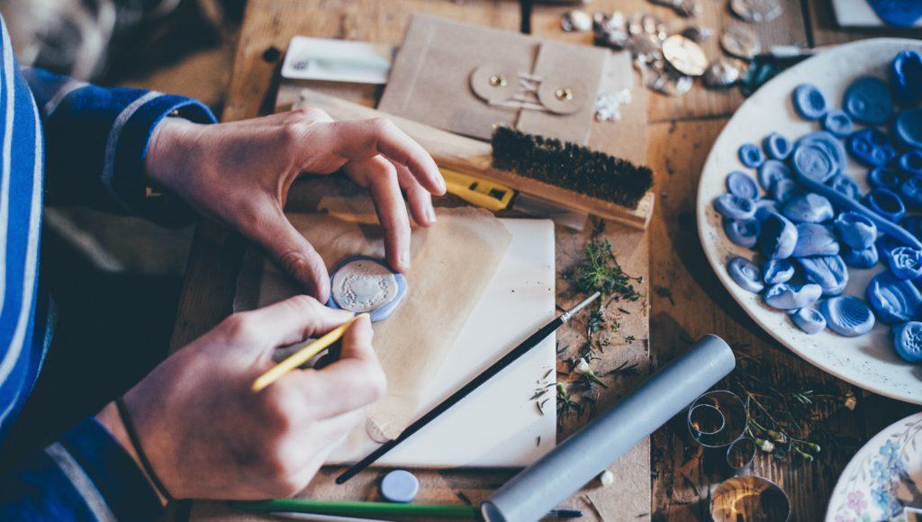 Stół w pracowni, a na nim różne materiały do prac ręcznych - szpikulce, szczotka, aplikacje do przyklejenia.Kobieta odrysowuje z szablonu kształt koła.