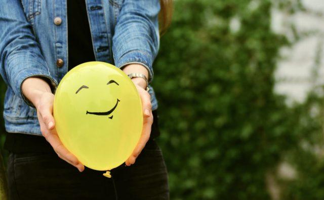Kobieta trzyma w ręku balonik z namalowanym uśmiechem