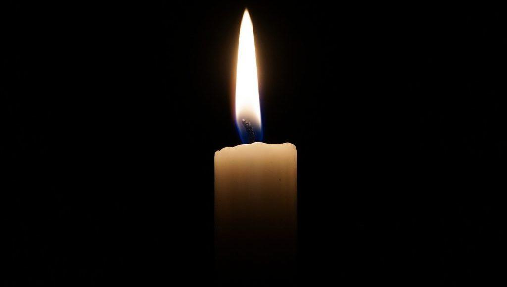 Płonąca świeca na czarnym tle.