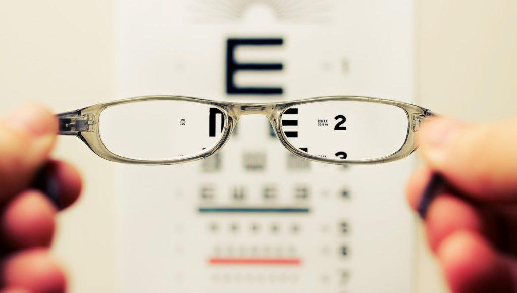 Gabinet okulistyczny. Tablica z literami i cyframi. Przed nią stoi osoba trzymająca w dłoniach szkła okularowe.