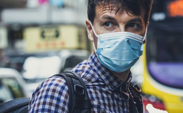 Mężczyzna w maseczce na twarzy stoi na ulicy miasta