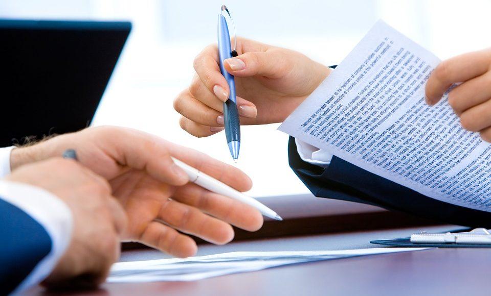 Dłonie dwóch osób zwrócone do siebie, trzymające długopisy