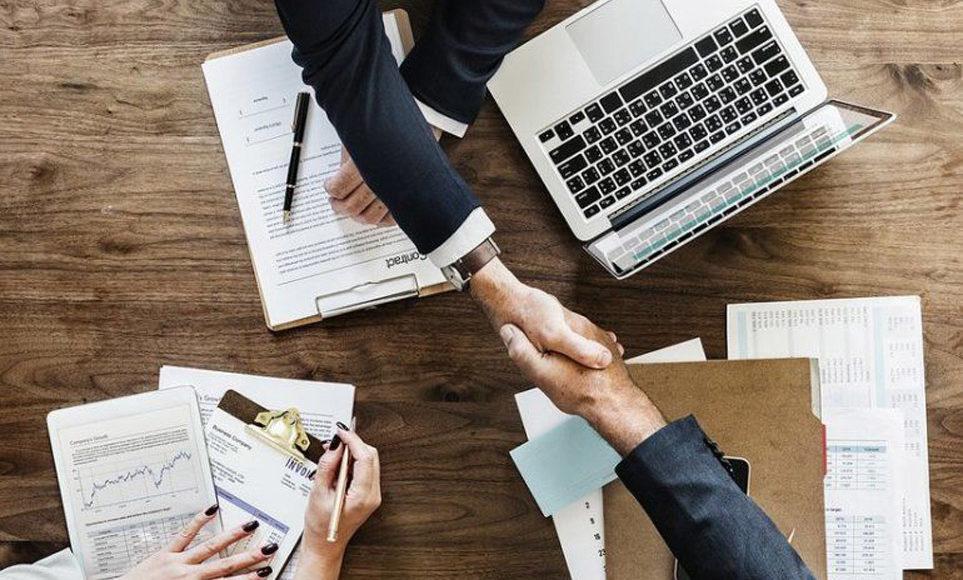 Spotkanie biznesowe. Na stole stoi laptop i leży wiele dokumentów. Dwie osoby ściskają sobie ręce.