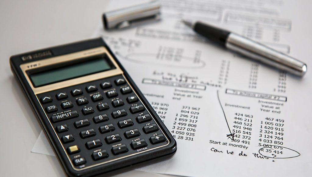 Kalkulator, kartka z obliczeniami i długopis.