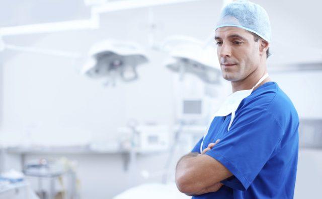 Lekarz w niebieskim kitlu, z czepkiem na głowie stoi w gabinecie.