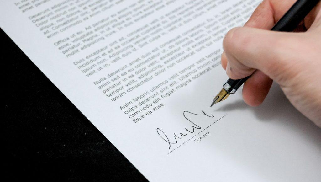 Zdjęcie. Ktoś podpisuje dokument.