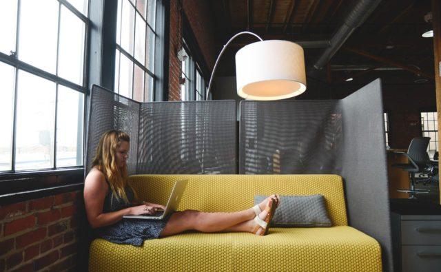 Młoda kobieta siedzi na kanapie z laptopem na kolanach