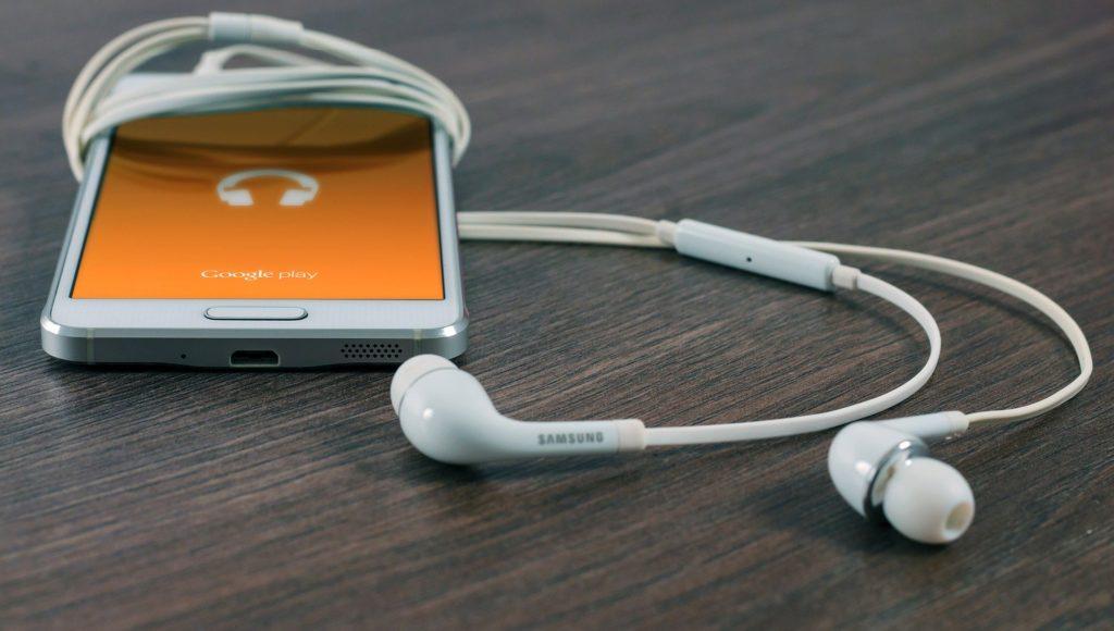 Telefon leży na stole, do niego podpięte są słuchawki.