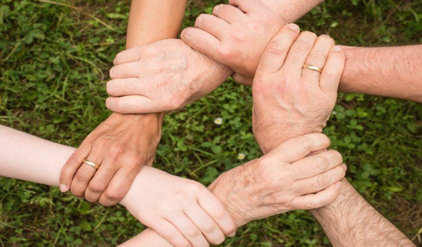Dłonie kilka osób złączone ze sobą.