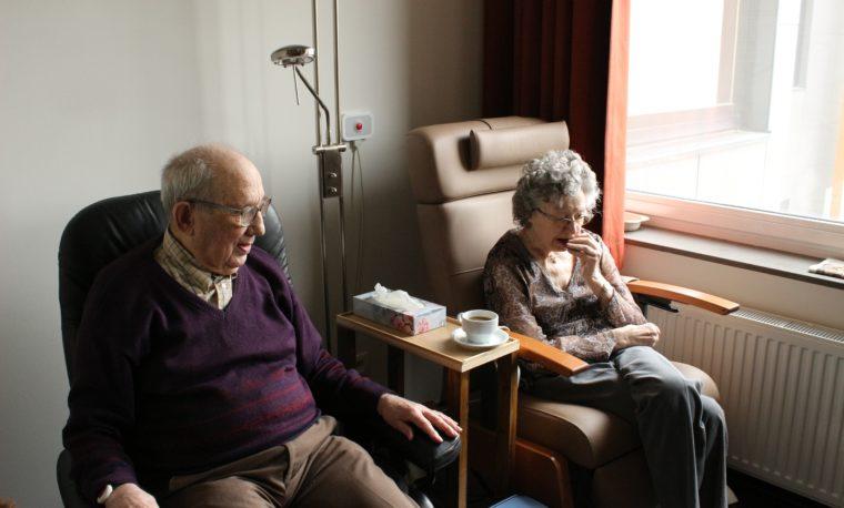 Dwie osoby starsze siedzą na fotelach w swoim pokoju