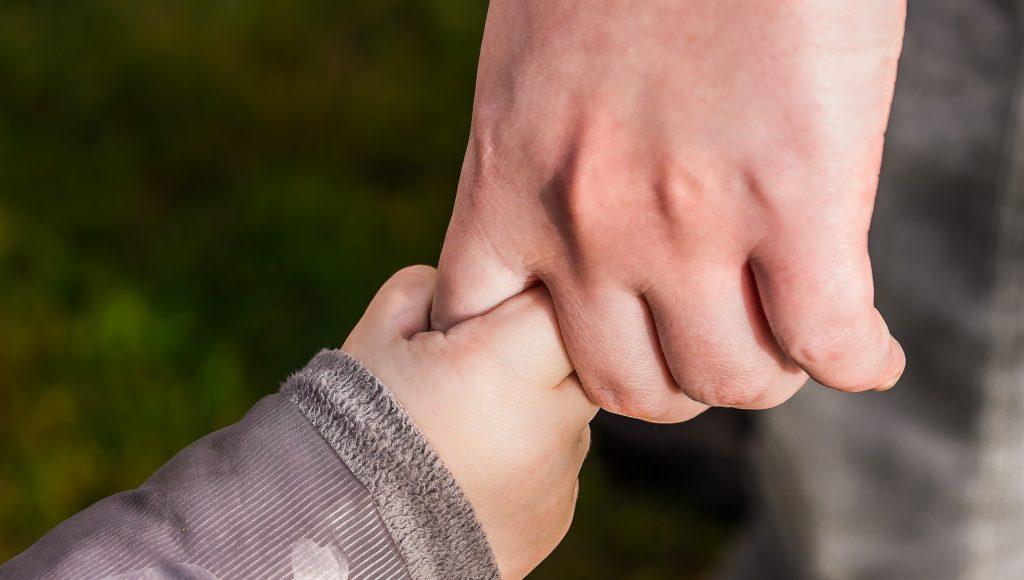 Mała rączka dziecko trzyma palec dorosłego