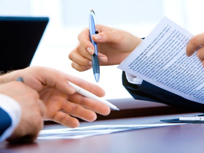 Zdjęcie. Najprawdopodobniej urząd. Jedna osoba trzyma w jednej dłoni dokument, w drugiej długopis. Druga osoba czeka na podpisanie dokumentu. W dłoni również trzyma długopis.