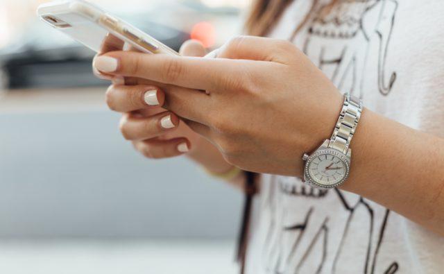 Kobieta trzyma smartphone w dłoni i wybiera numer