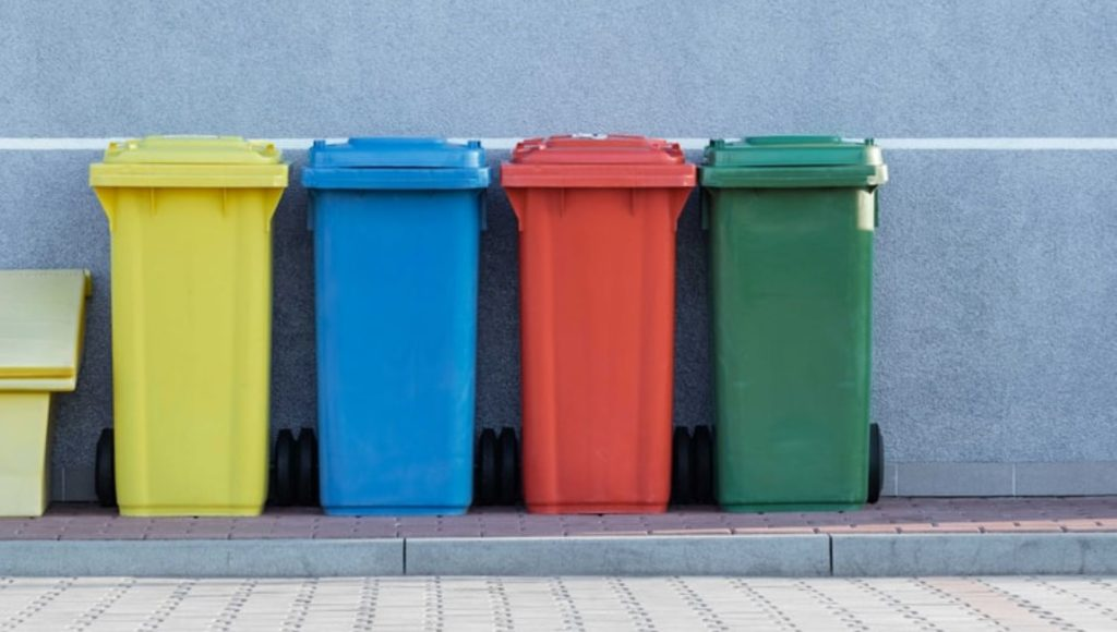 Cztery kosze na śmieci stojące przy ścianie. Od lewej: żółty, niebieski, czerwony i zielony.