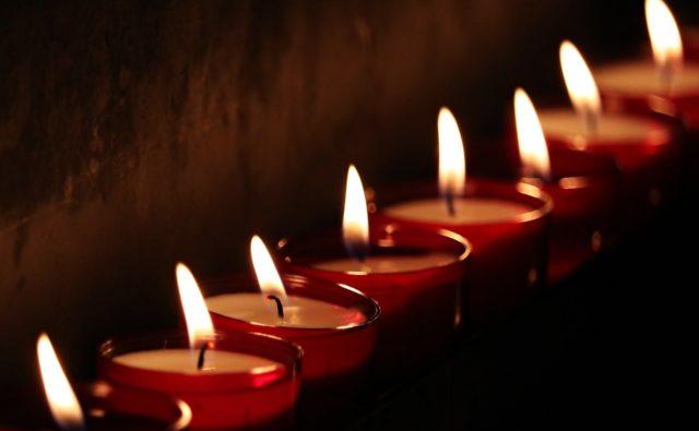 Zapalone świeczki stojące w rzędzie.