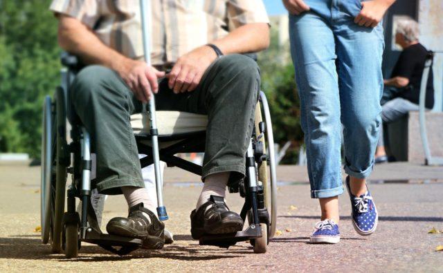 Dwie osoby - jedna na wózku inwalidzkim, trzyma w ręce laskę, obok niej stoi druga osoba.