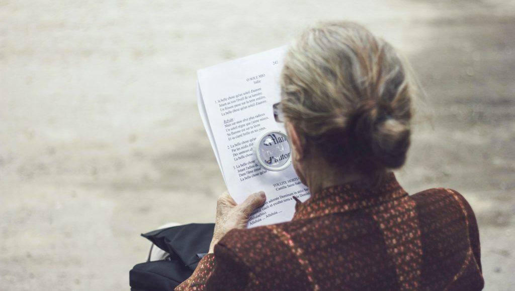 Kobieta uzywa lupy do przeczytania tekstu