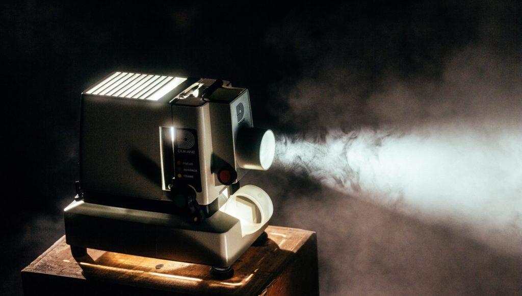 Zdjęcie. Projektor filmowy stoi na podwyższeniu. Jest włączony, wychodzi z niego smuga światła.