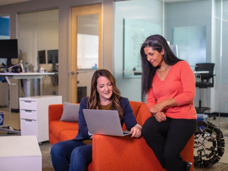 Kobiety w pracy przy laptopie omawiają jakiś problem