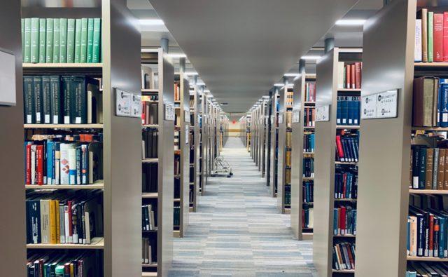 Zdjęcie. Korytarz w bibliotece. Po obu stronach rzędy regałów z książkami.