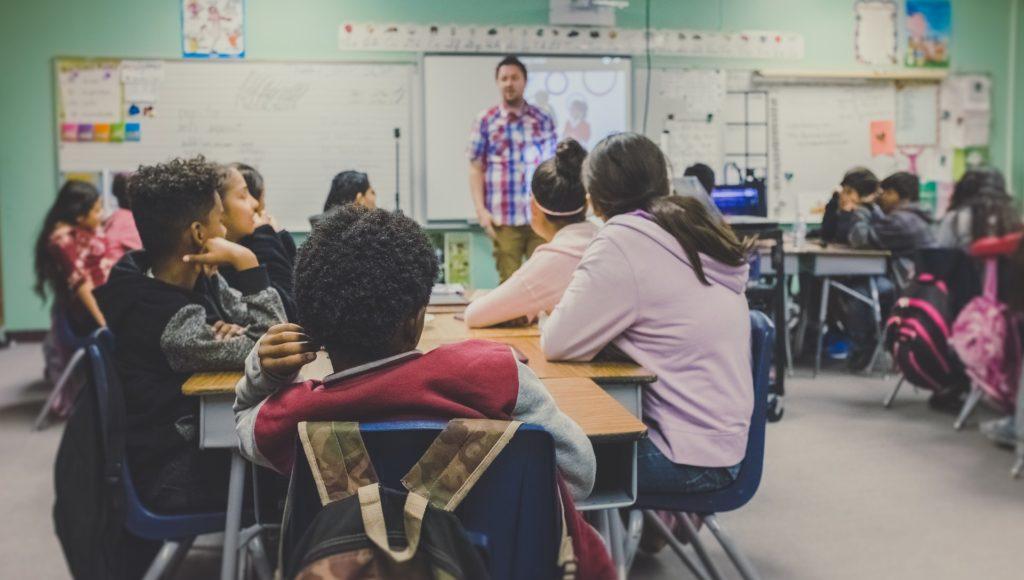 Zdjęcie. Klasa. Trzy grupy uczniów siedzą w ławkach - z lewej strony, na środku sali i z prawej strony. Na środku sali stoi nauczyciel.