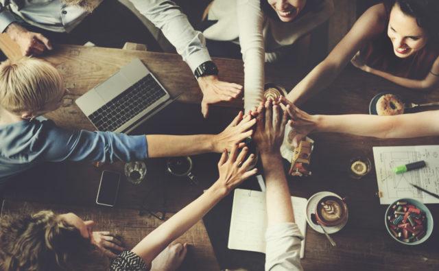 młode osoby podają sobie ręce na znak jedności
