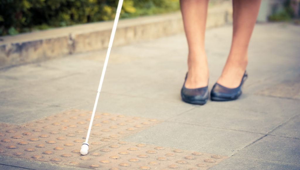 Kobieta niewidoma idzie z białą laską
