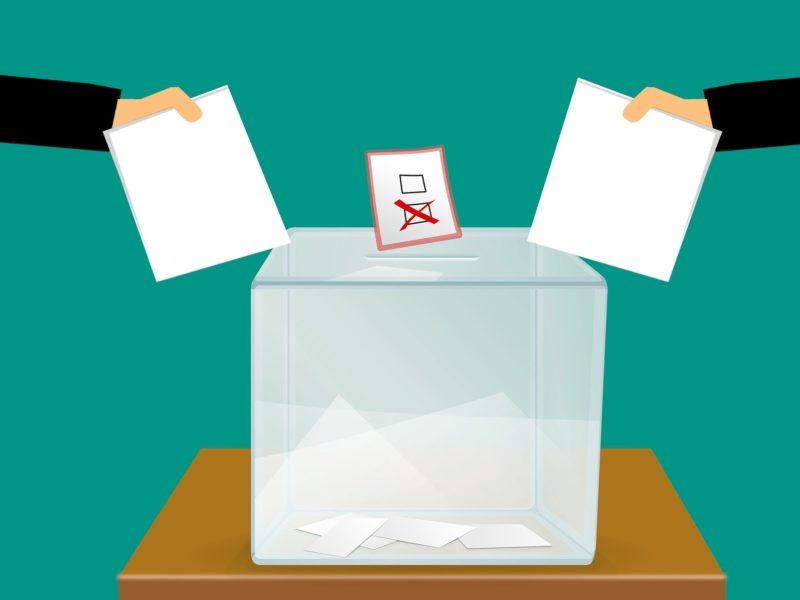 Rysunek. Urna wyborcza, w miejscu wyznaczonym na wrzucenie głosu tkwi karta do głosowania. Są na niej dwie kratki, jedna została oznaczona krzyżykiem. Z lewej i prawej strony urny wyłaniają się wyciągnięte ręce dwóch osób z kartami do głosowania.