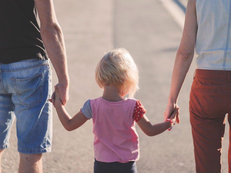 Rodzice trzymają małe dziecko za ręce.