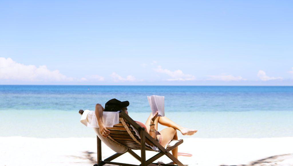 Kobieta relaksuje się siedząc w leżaku na plaży