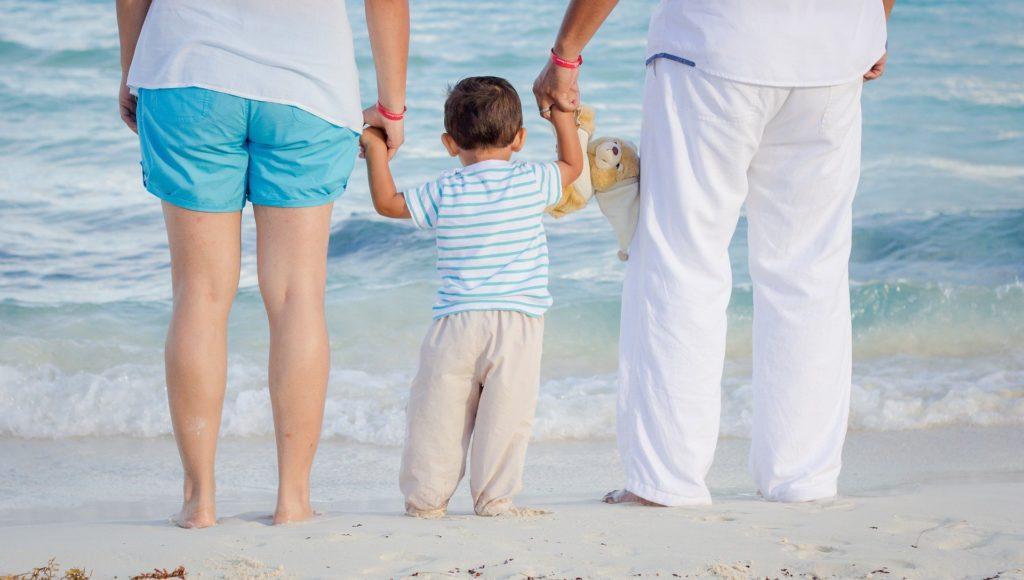 Rodzina nad morzem. Rodzice trzymają chłopca za ręce.