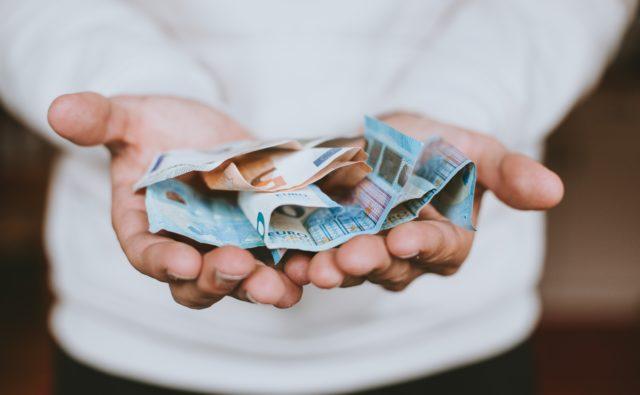 Osoba w otwartych dłoniach trzyma pieniądze