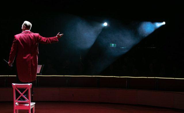 Na scenie teatru stoi aktor. Jest ubrany w czerwony płaszcz. Światła skierowane są w jego stronę.