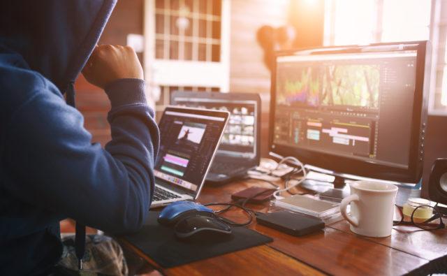 Zdjęcie. Mężczyzna siedzi przy biurku. Na nim znajdują się różne sprzęty: dwa laptopy, myszka, duży ekran.
