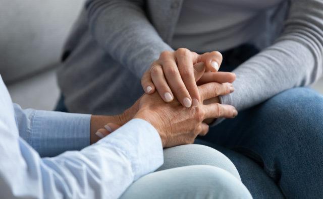 Jedna osoba trzyma drugą za rękę w geście wsparcia